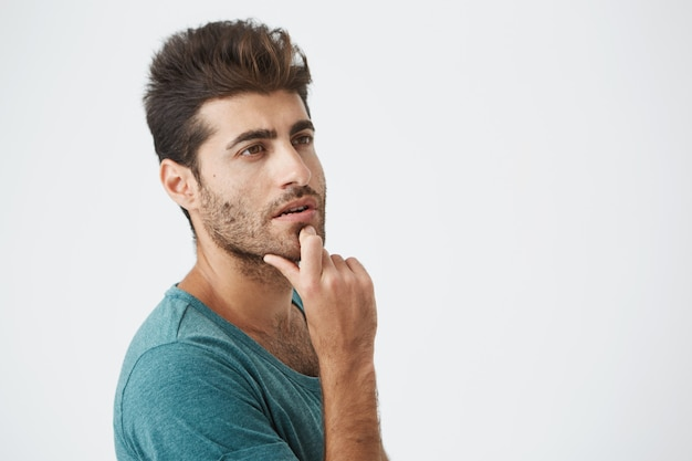 Schließen sie herauf porträt des gutaussehenden spanischen mannes im blauen t-shirt, der mit nachdenklichem ausdruck nach oben schaut und an abendessen für heute denkt. porträt. menschliche gesichtsausdrücke