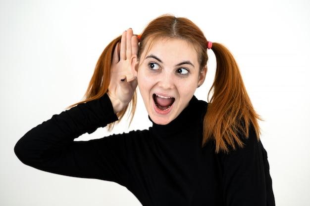 Schließen sie herauf porträt des hübschen rothaarigen teenager-mädchens, das eine hand an ihr ohr hält, das einem geheimnis lauscht