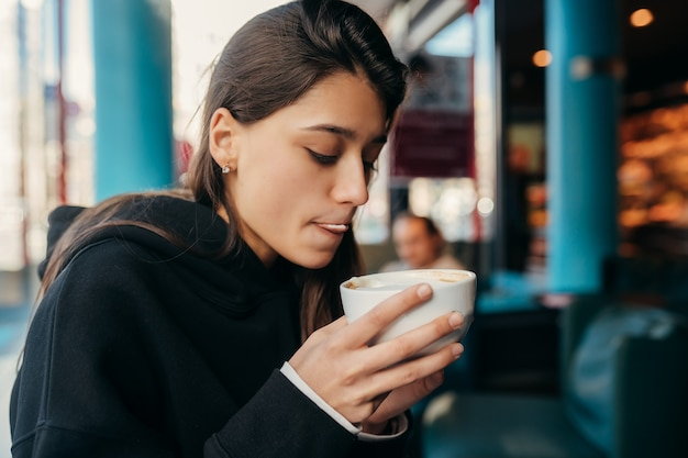 Schließen sie herauf porträt des hübschen weiblichen trinkkaffees. dame, die einen weißen becher mit der hand hält.