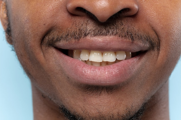 Schließen sie herauf porträt des jungen afroamerikanermannes auf blauer wand. menschliche emotionen, gesichtsausdruck, werbung, verkauf oder schönheitskonzept. fotoshooting der lippen. sieht ruhig aus, lächelt und zeigt die zähne.