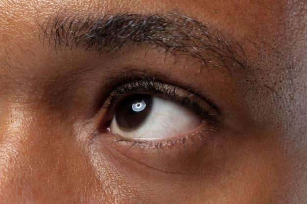 Schließen sie herauf porträt des jungen afroamerikanermannes auf blauer wand. menschliche emotionen, gesichtsausdruck, werbung, verkauf oder schönheitskonzept. fotoshooting eines auges. sieht ruhig aus und schaut auf.