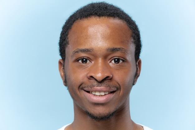 Schließen sie herauf porträt des jungen afroamerikanermannes im weißen hemd auf blauem raum