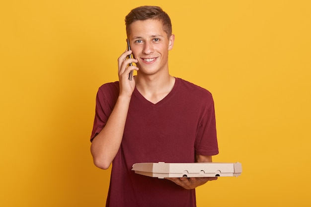 Schließen sie herauf porträt des jungen auslieferungsmannes, der pizzaschachteln in den händen hält und konversation über handy hat, lässig tragend, lächelnd in die kamera schauend, isoliert auf gelb posierend.