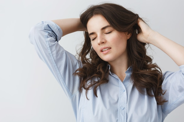 Schließen sie herauf porträt des jungen brünetten studentenmädchens mit den geschlossenen augen, die hände im haar mit ruhigen und sexy schwingungen halten.