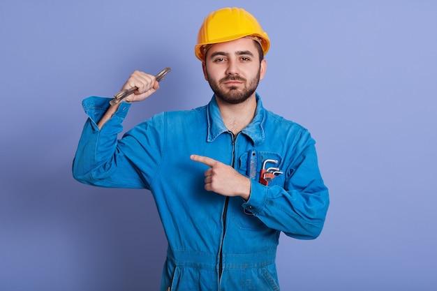 Schließen sie herauf porträt des jungen gutaussehenden arbeiters, der schraubenschlüsselwerkzeug in der hand hält und auf seinen starken bizeps zeigt