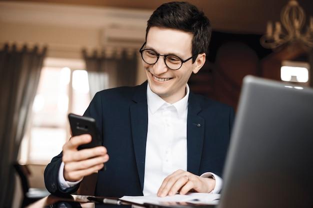 Schließen sie herauf porträt des jungen gutaussehenden mannes, der an seinem laptop auf einem schreibtisch arbeitet, während sie ein smartphone halten und den bildschirm lächelnd betrachten.