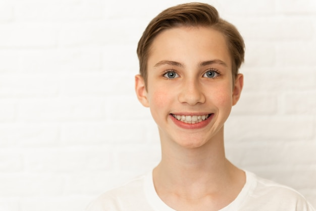 Schließen sie herauf porträt des jungen lächelnden niedlichen teenagers auf weißem hintergrund