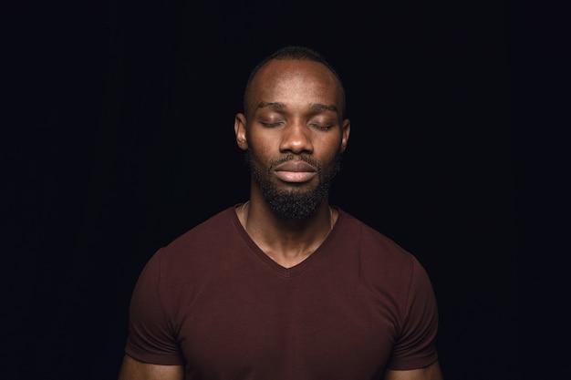 Schließen sie herauf porträt des jungen mannes lokalisiert auf schwarzem studiohintergrund. fotoshot von echten emotionen des männlichen modells mit geschlossenen augen. nachdenklich. gesichtsausdruck, menschliche natur und emotionskonzept.