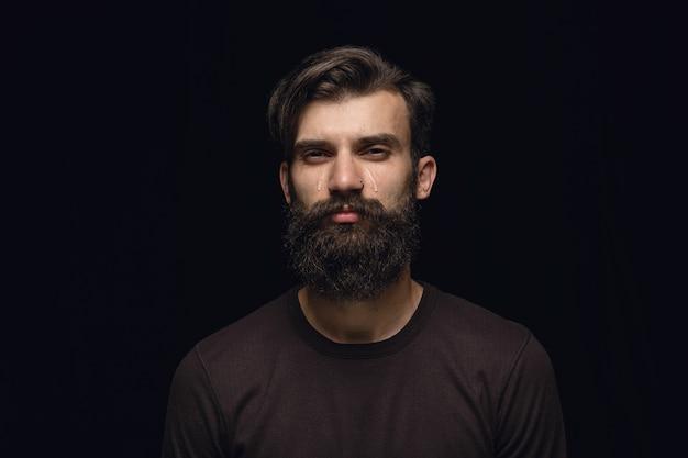 Schließen sie herauf porträt des jungen mannes lokalisiert auf schwarzraum. fotoshot von echten emotionen des männlichen models. weinen, traurig, trostlos und hoffnungslos