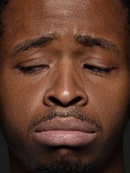 Schließen sie herauf porträt des jungen und emotionalen afroamerikanischen mannes. männliches model mit gepflegter haut und gesichtsausdruck. konzept menschlicher emotionen. verärgert, traurig, demotiviert.