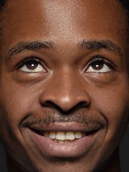 Schließen sie herauf porträt des jungen und emotionalen afroamerikanischen mannes. männliches model mit gepflegter haut und strahlendem gesichtsausdruck. konzept menschlicher emotionen. aufschauen und lächeln.