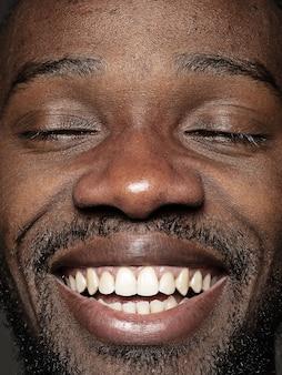 Schließen sie herauf porträt des jungen und emotionalen afroamerikanischen mannes. männliches model mit gepflegter haut und strahlendem gesichtsausdruck. konzept menschlicher emotionen. glückliches lächeln.