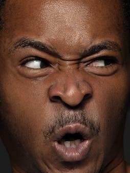 Schließen sie herauf porträt des jungen und emotionalen afroamerikanischen mannes. männliches model mit gepflegter haut und strahlendem gesichtsausdruck. konzept menschlicher emotionen.