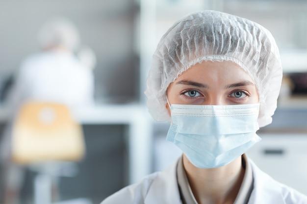 Schließen sie herauf porträt des jungen weiblichen sanitäters, der gesichtsmaske trägt und kamera während der arbeit im labor, kopierraum betrachtet