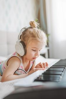 Schließen sie herauf porträt des kleinen blonden kleinkindmädchens, das weiße kopfhörer trägt, spielen klassisches digitales klavier zu hause, das auf bett liegt.