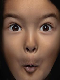 Schließen sie herauf porträt des kleinen und emotionalen asiatischen mädchens. hochdetailliertes fotoshooting eines weiblichen models mit gepflegter haut und strahlendem gesichtsausdruck. konzept menschlicher emotionen. sieht schockiert und erstaunt aus.