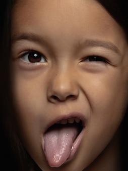 Schließen sie herauf porträt des kleinen und emotionalen asiatischen mädchens. hochdetailliertes fotoshooting eines weiblichen models mit gepflegter haut und strahlendem gesichtsausdruck. konzept menschlicher emotionen. zunge rumhängen.