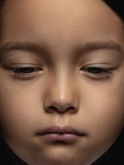Schließen sie herauf porträt des kleinen und emotionalen asiatischen mädchens. hochdetailliertes fotoshot eines weiblichen models mit gepflegter haut und strahlendem gesichtsausdruck. konzept menschlicher emotionen. sieht traurig und verärgert aus.