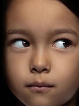 Schließen sie herauf porträt des kleinen und emotionalen asiatischen mädchens. hochdetailliertes fotoshot eines weiblichen models mit gepflegter haut und strahlendem gesichtsausdruck. konzept menschlicher emotionen. sieht verspielt aus und träumt.