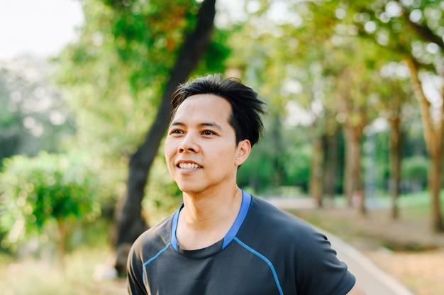 Schließen sie herauf porträt des lächelnden gesunden asiatischen mannes in der fitness tragen ruuning im park am morgen