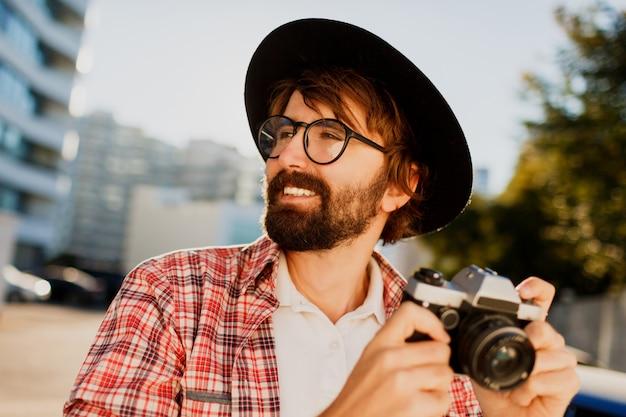 Schließen sie herauf porträt des lächelnden hipster-bartmannes unter verwendung der retro-filmkamera