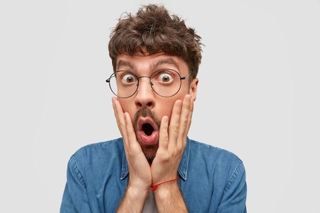 Schließen sie herauf porträt des lustigen bärtigen männlichen blicks mit überraschung, berührt wangen und öffnet mund, kann nicht an etwas glauben, isoliert über weißer wand. menschen- und emotionskonzept