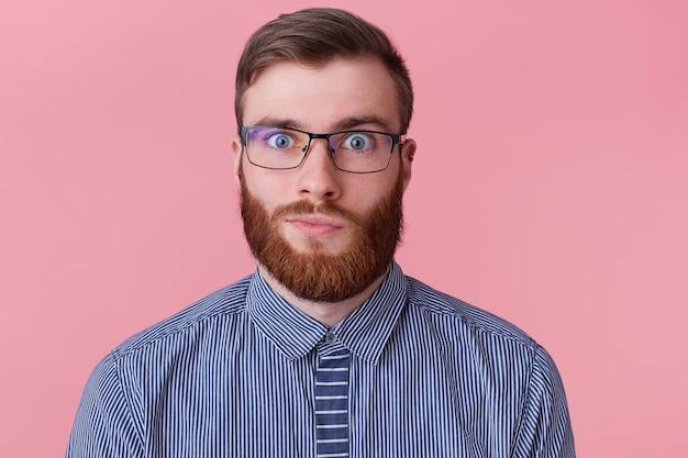 Schließen sie herauf porträt des lustigen ingwer-kerls in den gläsern und im gestreiften hemd, die kamera betrachten, lokalisiert auf rosa hintergrund.