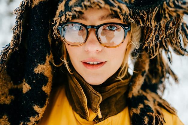 Schließen sie herauf porträt des lustigen jungen hipster-mädchens mit brille und dem schal, der den kopf bedeckt