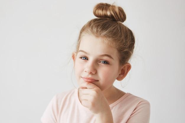 Schließen sie herauf porträt des lustigen mädchens mit blondem haar in der brötchenfrisur, finger am kinn haltend, mit interessiertem und foxy ausdruck.