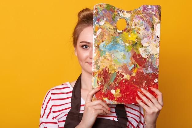 Schließen sie herauf porträt des malers der jungen frau gegen gelbe wand, zeichnet bild, dame, die lässiges gestreiftes hemd und braune schürze trägt