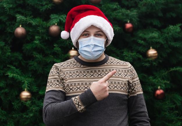 Schließen sie herauf porträt des mannes, der einen weihnachtsmannhut und eine medizinische maske mit emotion trägt und den finger zeigt. vor dem hintergrund eines weihnachtsbaumes. coronavirus pandemie