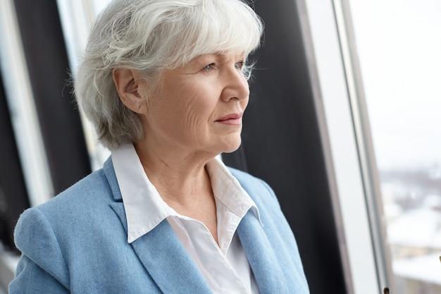 Schließen sie herauf porträt des modischen älteren europäischen weiblichen schriftstellers mit den weißen haaren, die drinnen aufwerfen und durch fenster mit tief in gedanken nachdenklichem blick schauen. menschen, lebensstil, altern und reife