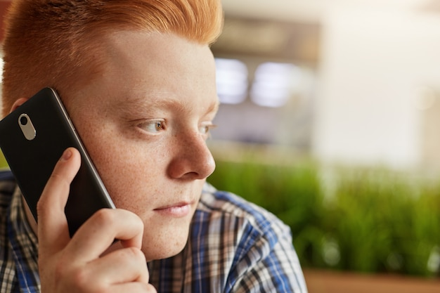 Schließen sie herauf porträt des modischen kerls mit den roten haaren, die sommersprossen auf seinem gesicht haben, die über das telefon sprechen, während sie im restaurant sitzen und nachdenklich beiseite schauen. menschen, mode, technologiekonzept.