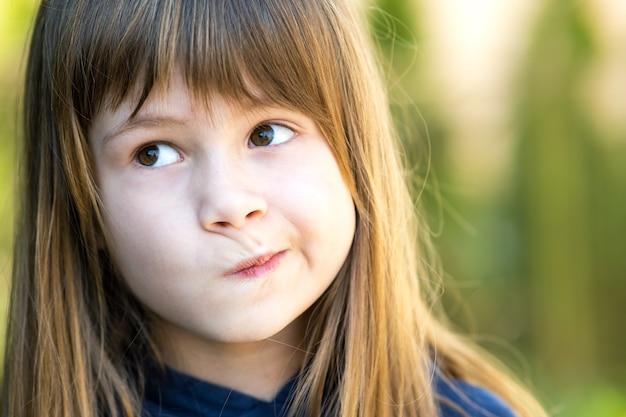 Schließen sie herauf porträt des nachdenklichen netten brunette-kindermädchens im park.