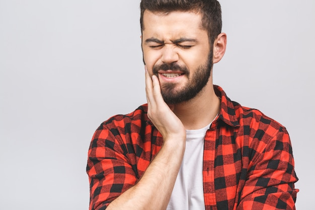 Schließen sie herauf porträt des nervösen unglücklichen unruhigen gutaussehenden bärtigen mannes, der seine wange berührt, er hat zahnschmerzen isoliert auf weißem hintergrundkopierraum.