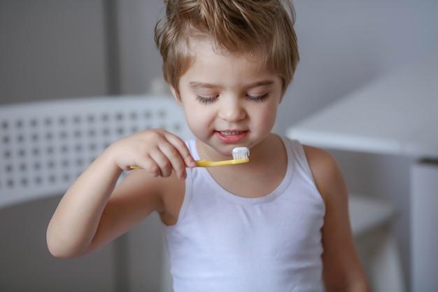 Schließen sie herauf porträt des netten, entzückenden, kleinkindjungen, der seine zähne mit einer zahnbürste putzt