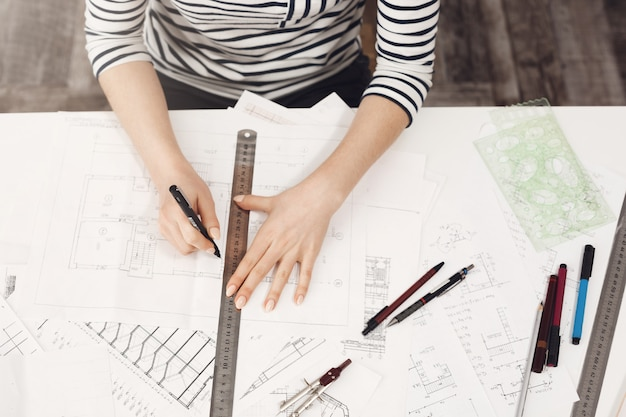 Schließen sie herauf porträt des professionellen jungen schönen weiblichen architekten in gestreiften kleidern, die ihre zeichnungen mit lineal und stift tun und mit interesse an neuem projekt arbeiten.