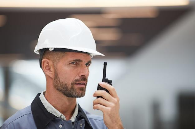 Schließen sie herauf porträt des reifen arbeiters, der durch walkie-talkie spricht, während sie arbeit auf der baustelle oder in der industriewerkstatt überwachen,