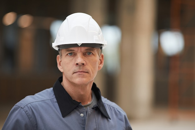 Schließen sie herauf porträt des reifen arbeiters, der helm trägt und während auf der baustelle oder in der industriewerkstatt steht,