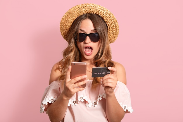 Schließen sie herauf porträt des schockierten emotionalen weibchens mit weit geöffnetem mund, das isoliert auf rosa im studio aufwirft, kreditkarte und smartphone in beiden händen hält und einkäufe tätigt.