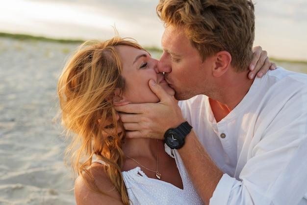 Schließen sie herauf porträt des schönen europäischen paares, das gegen sonnenuntergang umarmt. schließen sie herauf porträt des mannes und der frau zusammen, küssend und umarmend.