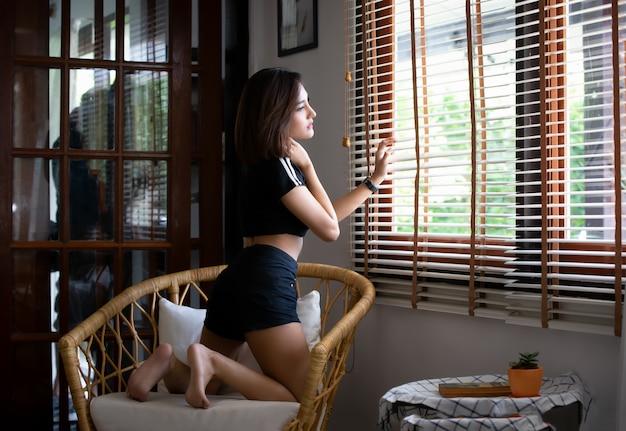 Schließen sie herauf porträt des schönen jungen mädchens in der sexy wäsche des schwarzen hemdes auf einem stuhl