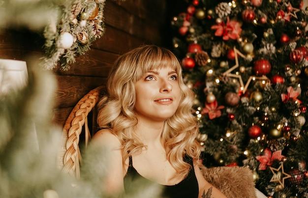 Schließen sie herauf porträt des schönen jungen mädchens mit dem langen lockigen haar auf einem weihnachtshintergrund mit lichtern. magisches warmes neujahrsfoto. gemütliches interieur.