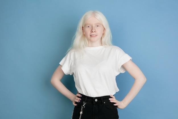 Schließen sie herauf porträt des schönen kaukasischen albino-mädchens auf blau. blondes weibliches modell mit stilvollem blick. konzept von gesichtsausdruck, menschlichen emotionen, kindheit, werbung, verkauf, vielfalt.