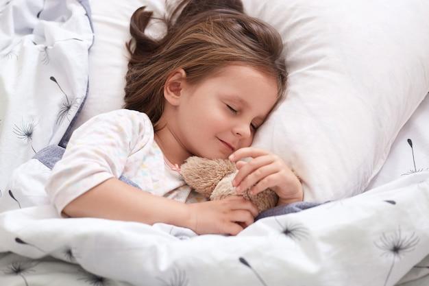 Schließen sie herauf porträt des schönen mädchens, das im pyjama im bett mit ihrem teddybär schläft, auf kissen mit geschlossenen augen liegend, charmantes niedliches weibliches kind, das dunkles haar hat. konzept für kindheit und morgenzeit.