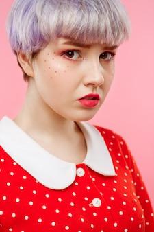 Schließen sie herauf porträt des schönen puppenmädchens mit dem kurzen hellen violetten haar, das rotes kleid über rosa wand trägt