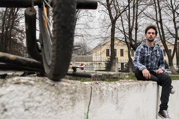 Schließen sie herauf porträt des stilvollen hübschen hippie-kerls, der am stadtpark nahe seinem fahrrad sitzt