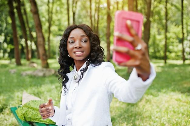 Schließen sie herauf porträt des stilvollen schwarzafrikanermädchens, das selfie mit rosa handy nimmt