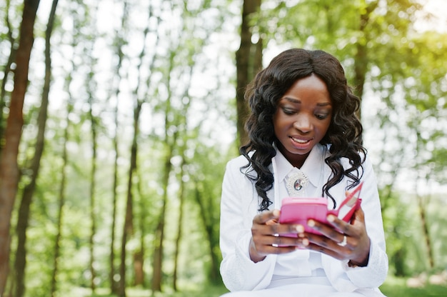 Schließen sie herauf porträt des stilvollen schwarzafrikanermädchens mit rosa handy