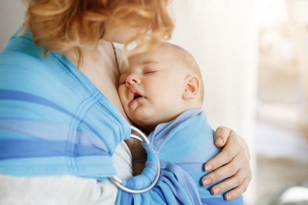 Schließen sie herauf porträt des unschuldigen neugeborenen jungen, der süße träume auf mutterbrust in babyschlinge hat. mutter, die ihr kind mit liebe und zärtlichkeit ansieht.